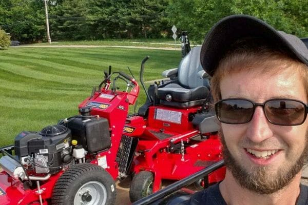 Headshot of Billy the owner of B N B Lawn Mowing with his trailer, lawn mowers, and a lawn he just cut in the background.