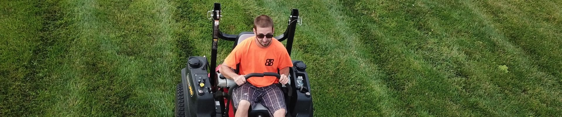 Drone photo of Billy with B N B Lawn Mowing on his zero turn mower mowing a lawn.