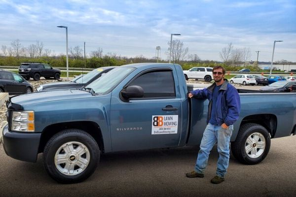 BNB Lawn Mowing's owner posing with their new slate grey Chevy lawn care truck.