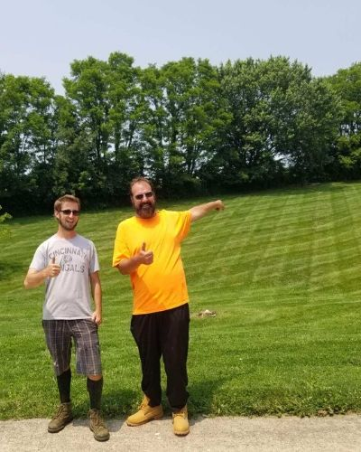 BNB Lawn Mowing owner with a satisfied client posing for a picture in front of his professionally mowed lawn.